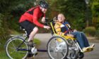 James Murray of Kirkhill on his wheelchair bike with brother in law Mark Forbes at the pedals.