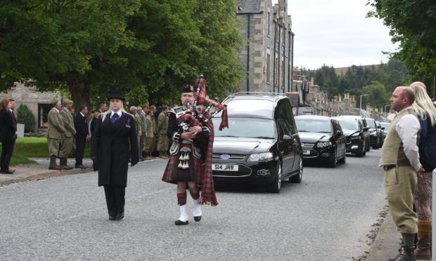 After a private family funeral, the cortege, led by a piper, made its way down the main street in Tomintoul to the local cemetery.
