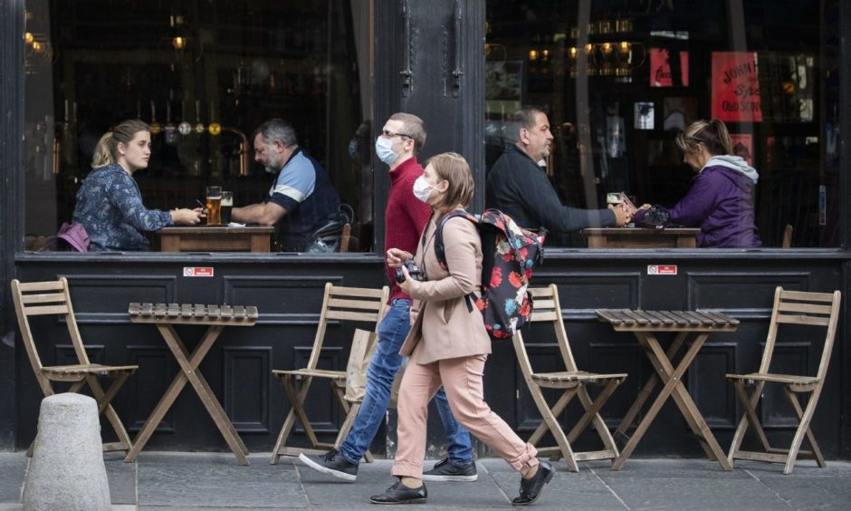 People wearing protective face masks walk past a bar.
