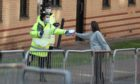 NHS staff hand out test kits to Glasgow University students as they arrive for testing at a pop up test centre