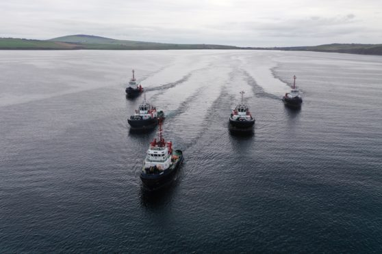 The two new tugs arrive in Scapa Flow, escorted by the three currently in service