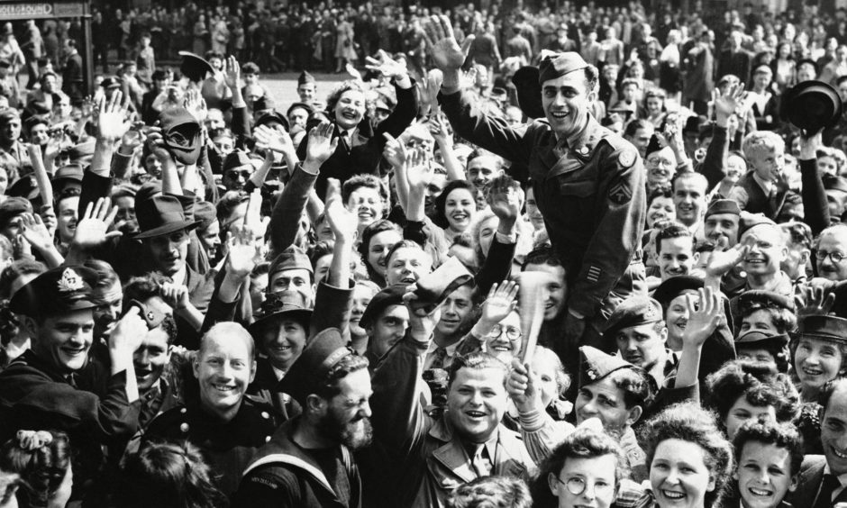 A jubilant crowd celebrates on hearing of the Japanese surrender on VJ Day in 1945, a date referenced by the first minister.