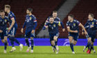 Scotland players run for Kenny McLean after he nets the decisive spot-kick.