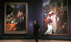 Actor Ellice Stevens poses next to the works (left) Annunciation and Saint Januarius by Italian Baroque painter Artemisia Gentileschi born in the 16th century.