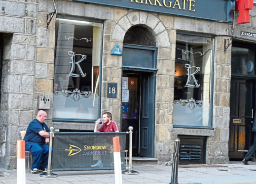 Pub goers drinking outside at the Kirkgate bar in Aberdeen.  Picture by Jim Irvine.