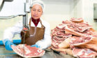 A meat plant worker preparing raw meat for processing and cutting.