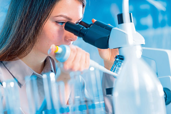 Scientist using a microscope in a laboratory.