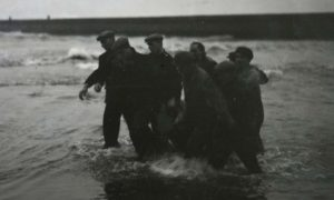 Rescuers bring a body ashore at Arbroath beach following the tragedy in 1953.