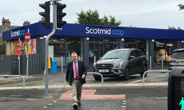 MSP David Stewart using the newly installed puffin crossing on the A82 on Glenurquhart Road at Smith Avenue, near the Scotmid store.