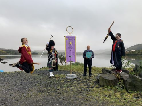 Eilidh Murray, Drum Major Peter MacDonald, councillor John Finlayson and Seamus MacDonald with the Quidditch banner.