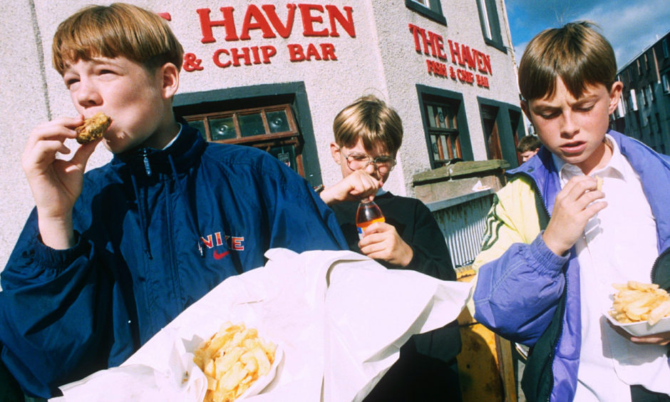 A group of young lads enjoying deep-fried Mars Bars from The Haven Fish and Chip Bar in 1999.