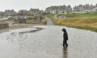 Waves caused flooding at the car park at Lossiemouth's West Beach. Picture by Jason Hedges.