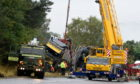 A crane in the process of removing the timber lorry