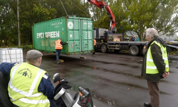 Dingwall Mens Shed members Raymond Jackson (left) and Steve Dovey watch as a container is unloaded.