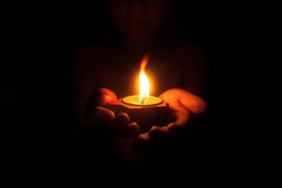 Little child holding burning candle in darkness with noise and grain effect.; Shutterstock ID 1158296245