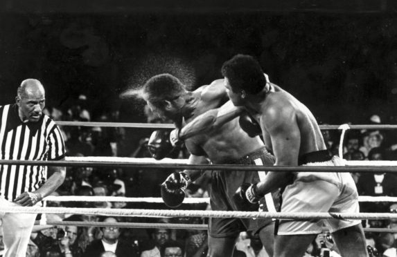 Perspiration flies from the head of George Foreman as he takes a right from challenger Muhammad Ali in the seventh round in the match dubbed Rumble in the Jungle in 1974.
