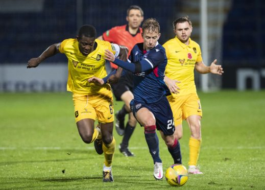 Ross County's Harry Paton holds off Marvin Bartley.