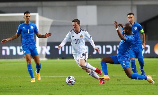 Callum McGregor drives forward against the Israel defence.