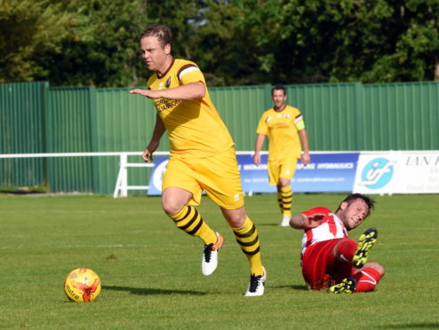 Forres' Simon Allan breaks away from the Formartine defence in the second half at North Lodge Park.