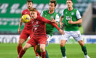 Brora's Andrew MacRae (L) holds off Hibernian's Melker Hallberg during a League Cup match at Easter Road last season.