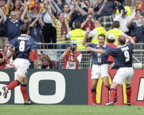 John Collins is hailed by Gordon Durie (right) and Craig Burley after equalising for Scotland from the penalty spot.