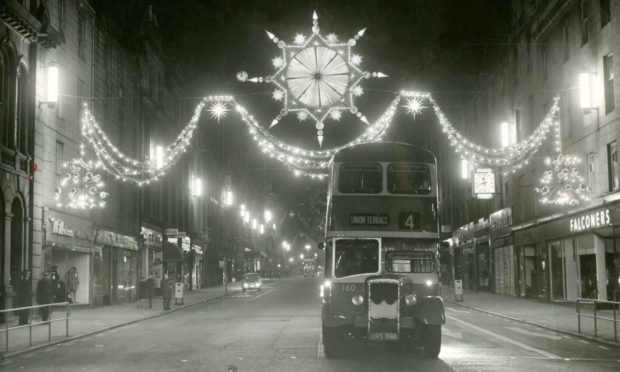 A number four bus drives along Union Street under the bright Christmas illuminations in 1964.