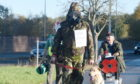 Picture by SANDY McCOOK  6th November '20  Former Gordon Highlander Gordon MacMillan on his walk from the Cameron Barracks in Inverness to the Inverness War memorial at Cavell Gardens in full NBC suit including a gas mask in aid of the Poppy Appeal with him is his Labrador Elsa.  Also in the photograph is former colleague Chad Fraser Hall, formerly of the Royal Greenjackets.