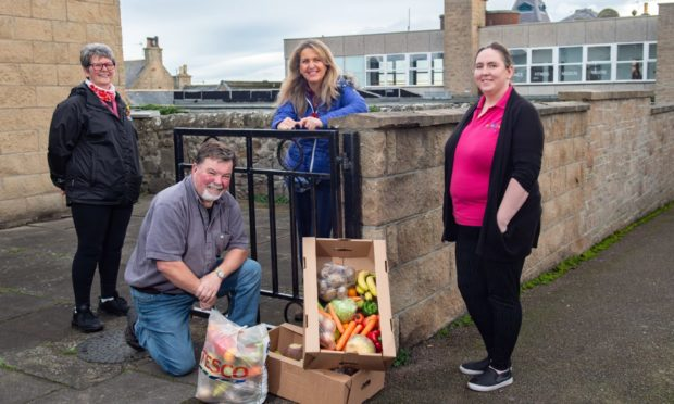 Daphne Thomas, volunteer for delivering meals and chairwoman of the Senior Citizen Christmas party, Neil Cameron, chairman of Lossie 2 to 3 group, Lossiemouth community councillor Carolle Ralph and Louise McBride, manager of the Lossie 2 to 3 Group