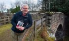 Dr William K Malcolm poses with his book on a bridge near his home in Aberlour
