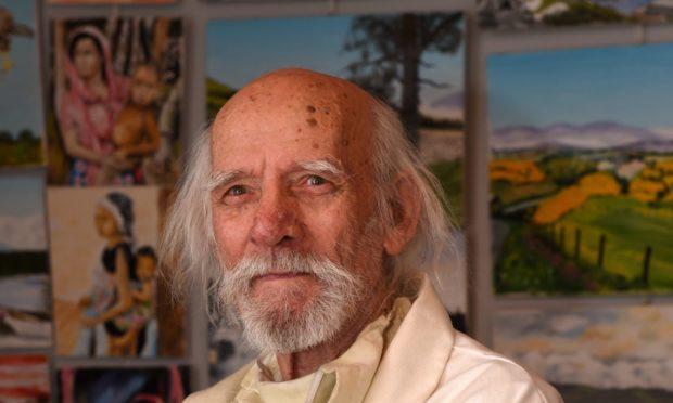 Artist Van Leiper in front of his paintings