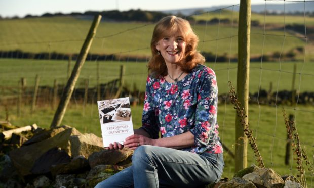 Professor Marjory Harper with her book Testimonies of Transition: Voices from the Scottish Diaspora.