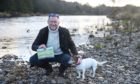 """Nicoll Johnston and Maggie by the River Dee with his newly published children's book """"There's a Path""""."""
