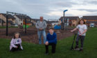 Buckie Riverside Church pastor John Coppard and the youngsters who have launched a petition urging Springfield to upgrade playpark in Seafield Estate in Buckpool by getting goalposts and a skate park.