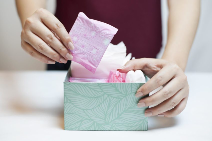 Closeup photo of young woman picking sanitary pad out of green box; Shutterstock ID 528070513; Purchase Order: My Weekly - December 19; Job: Dr Sarah Jarvis