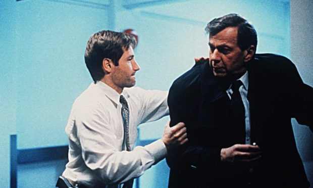 David Duchovny as Fox Mulder with William B Grant in a scene from The X-Files.