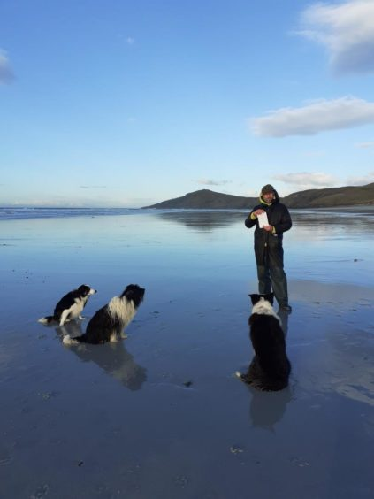 Michael Cox with the message and his dogs on Traigh Eais beach, Barra.