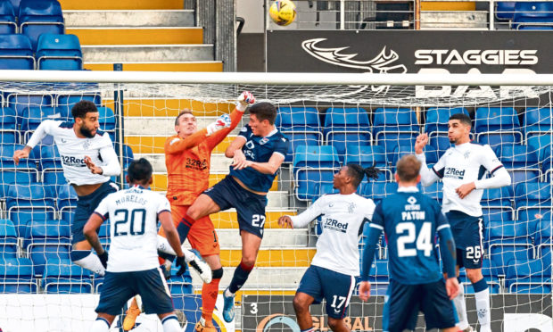 Rangers goalkeeper Allan McGregor punches the ball clear from Ross Stewart of Ross County during their Premiership match.