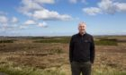 Calum MacDonald with Point and Sandwick Trust's Beinn Ghrideag turbines in the background.