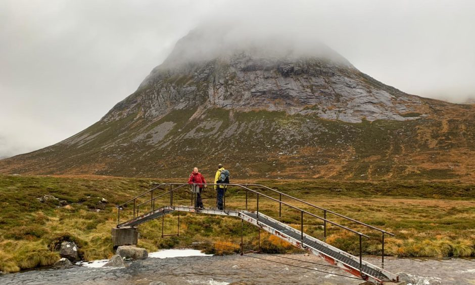 The two scientists assess a bridge over the Dee in the Cairngorms.
