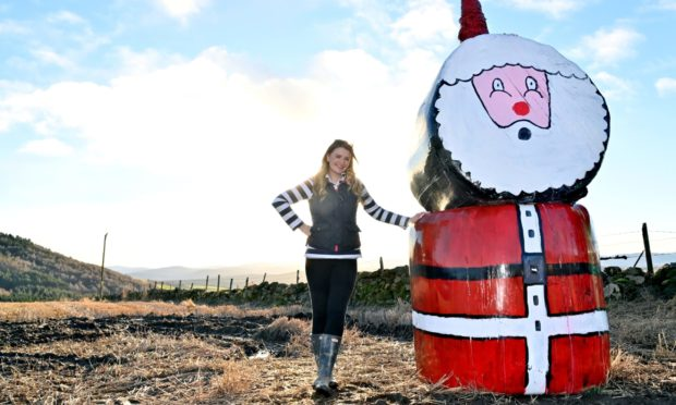 Jenna Ross with the Christmas silage bale Santa in Tarland