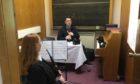Former Queen's piper Derek Potter using an electronic chanter to teach