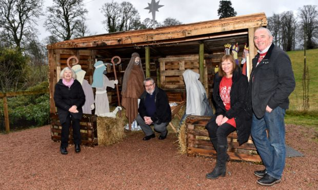 From left: Anne Harrison (session clerk), Euan Glen (Minister) with Lynda and Scott Langlands at their nativity scene barn at Cluny Parish Church, Inverurie.