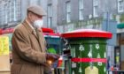 A man posts a card into the festive postbox on Union Street. Picture from Royal Mail