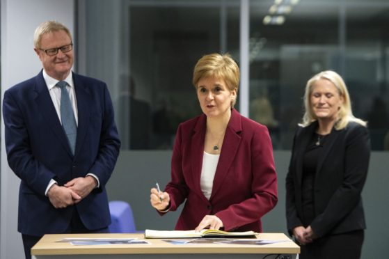 EMBARGOED TO 0001 MONDAY NOVEMBER 23  Scotland's First Minister Nicola Sturgeon  flanked by  Scottish National Investment Bank CEO Eilidh Mactaggart and chair Willie Watt signs a visitors book at the bank's official launch at their headquarters in Edinburgh, Scotland. PA Photo. Picture date: Thursday November 19, 2020. Photo credit should read: Andy Buchanan/PA Wire