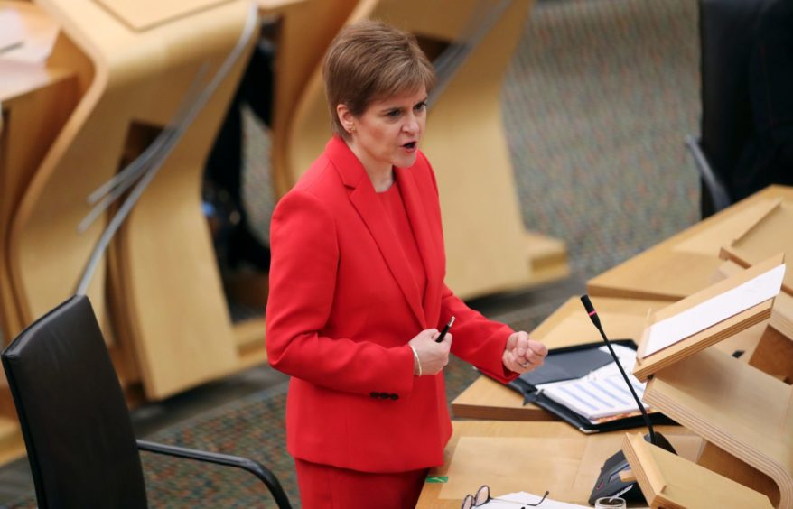 First Minister Nicola Sturgeon giving an update on Covid restrictions in the Scottish Parliament, Edinburgh. PA Photo. Picture date: Tuesday December 22, 2020. See PA story SCOTLAND Coronavirus. Photo credit should read: Russell Cheyne/PA Wire