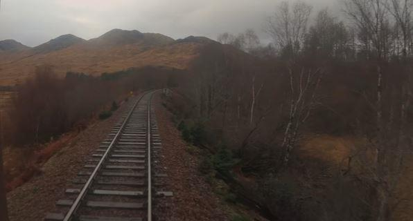 The train passing mountains on the approach to the Glenfinnan Viaduct.