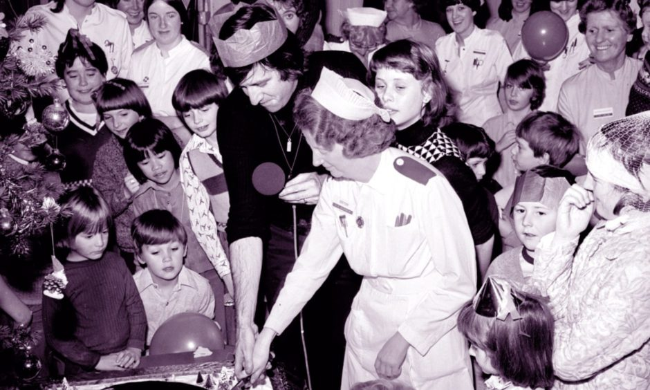 Radio 1 DJ Ed Stewart cuts a special Christmas cake with the help of Sister M Glennie after recording a radio programme in Ward 3 of the Royal Aberdeen Children's Hospital in 1978.
