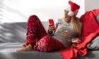 Woman sit on grey sofa in Christmas pyjamas and funny cap, with phone and talking with frienShutterstock
