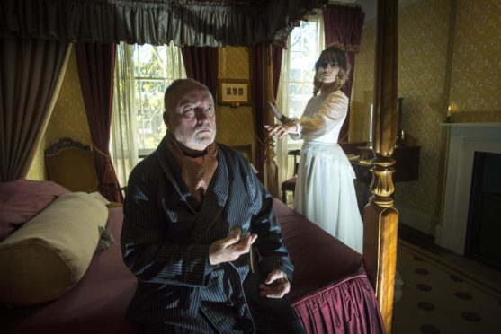Mandatory Credit: Photo by Geoff Pugh/Shutterstock (7532341h) Actors Julian Bird as Scrooge and Sarah Jackson as the ghost of Christmas past in the bedroom. Victorian Christmas at Charles Dickens Museum, London, UK - 29 Nov 2016 Dickens' former home is dressed for Christmas starting a month of events including candlelit visits, late night openings and performances. Actor, Sarah Jackson sits by the tree in the sitting room.
