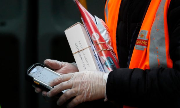 A Royal Mail employee wears gloves as he holds parcels and a handheld device.